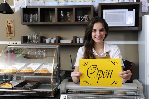 owner of a cafe showing open sign